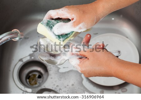 Woman hand washing spoon over the sink in the kitchen - stock photo