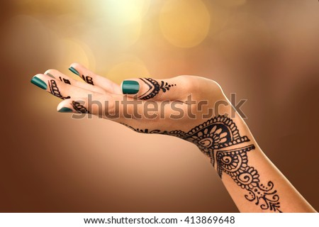 Woman Hand with black mehndi tattoo. Hand of Indian bride girl with black henna tattoos. Showing empty copy space on the open hand. Proposing a product. Advertising gesture over brown blurred bokeh