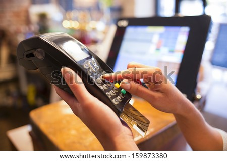 Woman hand with credit card swipe through terminal for sale in restaurant - stock photo