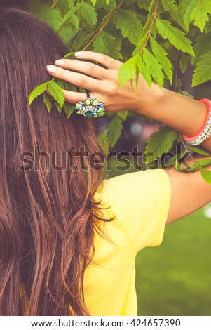 woman hand with large ring touch leaf and hair  outdoor shot closeup