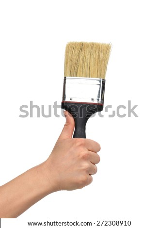 Woman hand with paint brush with plastic black handle isolated on a white background - stock photo