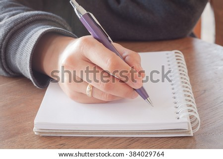 Woman hand with pen writing on notebook with vintage style