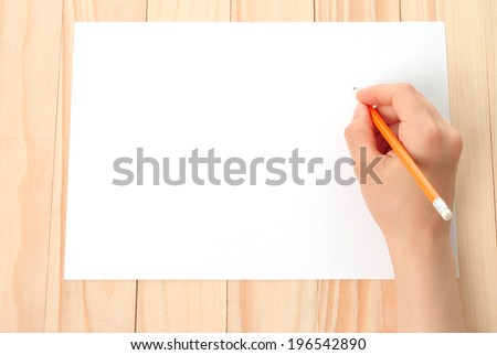 Woman hand with pencil and paper on wooden background   - stock photo