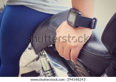 Woman hand with smartwatch on motorcycle