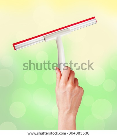 woman hand with special squeegee for cleaning over bright background - stock photo