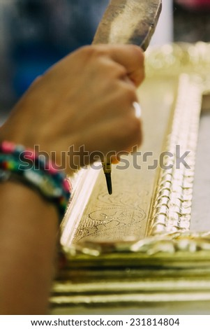 Woman hand working on a decoration of a wooden picture frame - stock photo