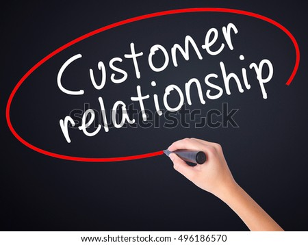 Woman Hand Writing Customer relationship on blank transparent board with a marker isolated over black background. Business concept. Stock Photo