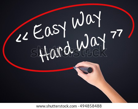 Woman Hand Writing Easy Way - Hard Way on blank transparent board with a marker isolated over black background. Stock Photo