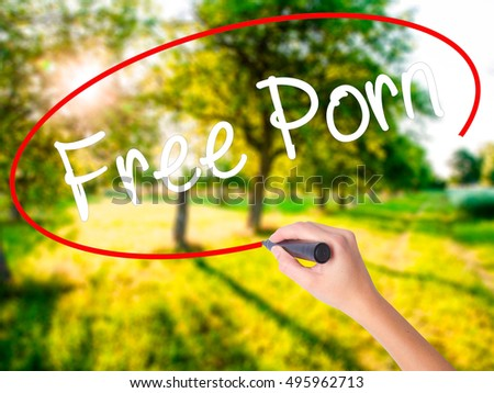 Woman Hand Writing Free Porn on blank transparent board with a marker isolated over green field background. Stock Photo