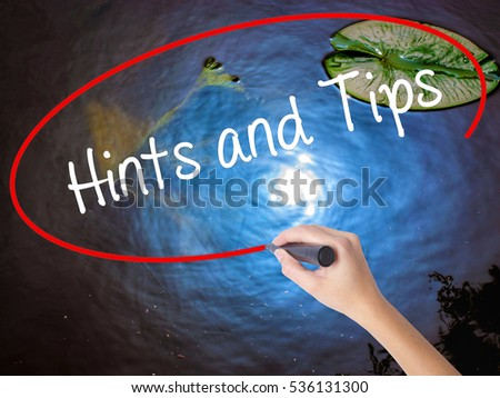 Woman Hand Writing Hints and Tips with marker over transparent board. Isolated on nature. Business concept. Stock Photo