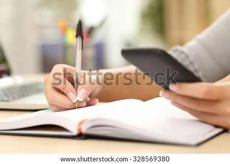 Woman hand writing in agenda consulting a mobile phone on a desk at home or office - stock photo