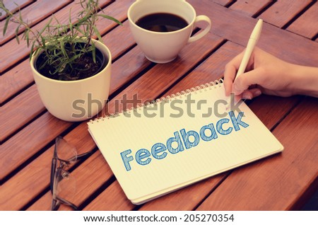 Woman hand writing in notebook Feedback on wooden table with coffee, plant and glasses. Retro colors. - stock photo