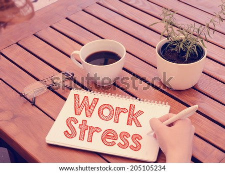 Woman hand writing in notebook Work Stress on wooden table with coffee, plant and glasses. Retro colors. - stock photo