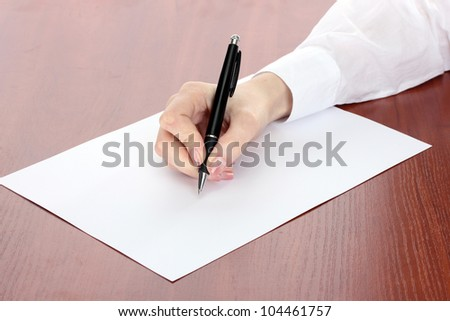 woman hand writing on paper, on wooden table