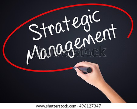 Woman Hand Writing Strategic Management on blank transparent board with a marker isolated over black background. Stock Photo