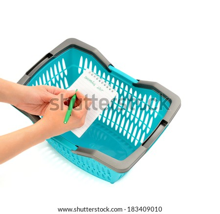Woman hand writing the shopping list and a blue market basket. Going to the market and making a list before concept. Isolated on white. - stock photo