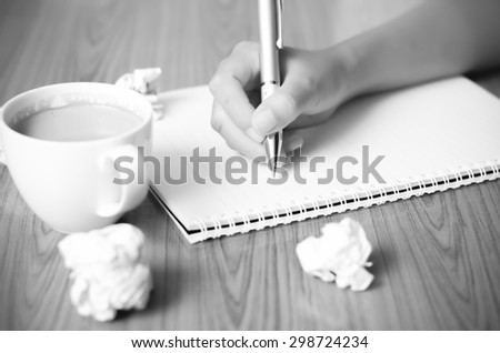 woman hand writing with pen on notebook.there are crumpled paper and coffee cup on wood table background black and white color tone style - stock photo