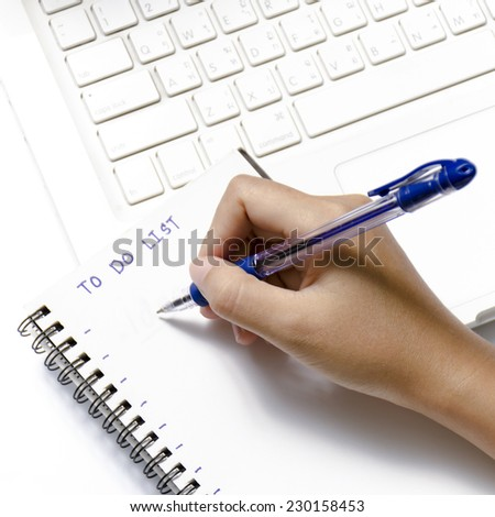 woman hand writing with pen on notebook write to do word and laptop over white background
