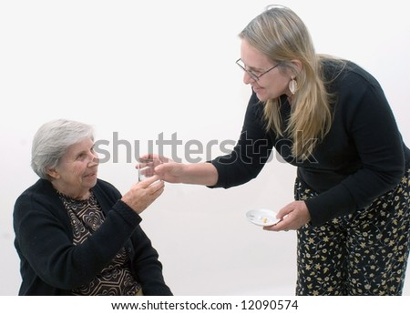 Woman handing her mother a glass of water and her medication. Isolated against a white background