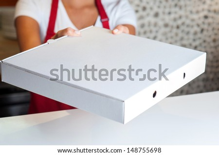Woman handing over pizza, cropped image. - stock photo