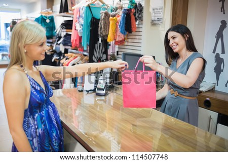 Woman handing over shopping bag at chas register in clothes store - stock photo