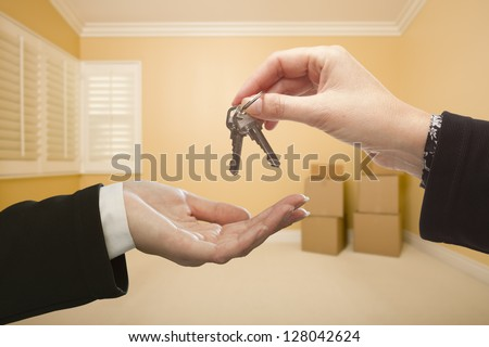 Woman Handing Over the House Keys To A New Home Inside Empty Room. - stock photo