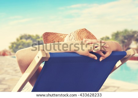 woman hands and hat and blue chair