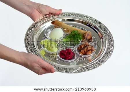 Woman hands carry Passover Seder Plate with The seventh symbolic item used during the Seder meal on passover Jewish holiday. On white background with copyspace - stock photo