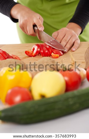 Woman hands chopping vegetables on a wooden board