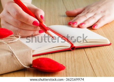 Woman hands drawing or writing, gift box, red hearts on wooden table - stock photo