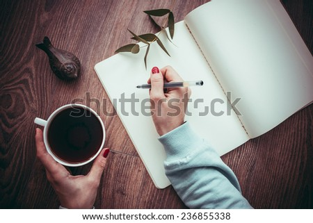 Woman hands drawing or writing in open notebook on wooden table. Toned picture - stock photo