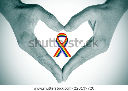 woman hands forming a heart ina black and white and a bright rainbow ribbon in the space  - stock photo