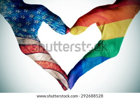 woman hands forming a heart patterned with the rainbow flag and the flag of the United States, depicting the legalization of the same-sex marriage in this country - stock photo