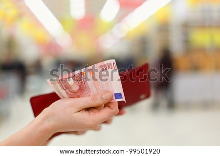 Woman hands gets money from her red purse in store; shallow depth of field - stock photo