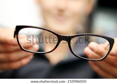 woman hands hold eyeglasses in front of her - stock photo