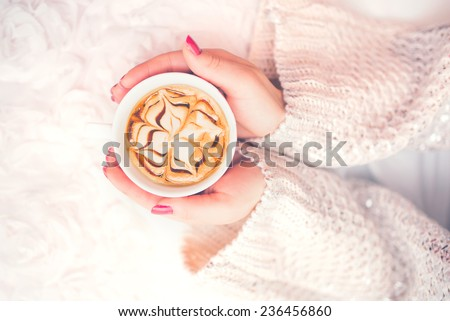 Woman hands holding a cup of hot coffee, espresso on a winter, cold day. View from top, soft vintage effect - stock photo