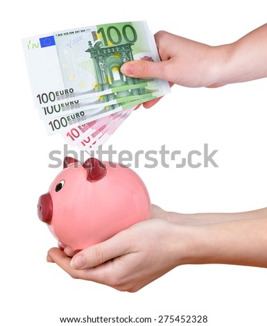 Woman hands holding a pink piggy bank and euro banknotes isolated on white background