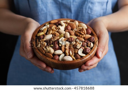 Woman hands holding a wooden bowl with mixed nuts. Healthy food and snack. Walnut, pistachios, almonds, hazelnuts and cashews. - stock photo