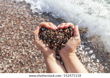 Woman hands holding colorful stones in heart shape
