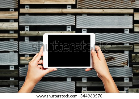 Woman hands holding electronic tablet pc with blank screen. Isolated against texture wall background with copy space.  - stock photo