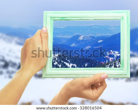 Woman hands holding empty frame on nature background