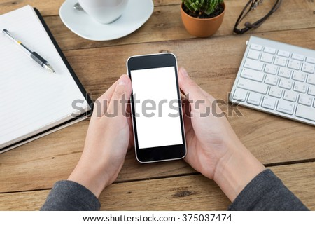 woman hands holding empty screen of smartphone on wood desk work. - stock photo