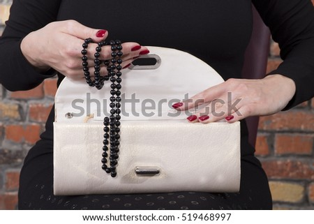 Woman hands holding fancy clutch with black pearl