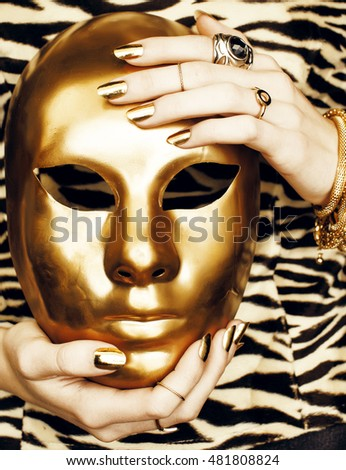 woman hands holding golden carnival halloween mask, rich luxury manicure and jewelry close up on zebra print, fashion clothers for people