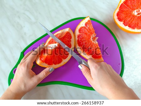 Woman hands holding knife and grapefruit on a cutting board.