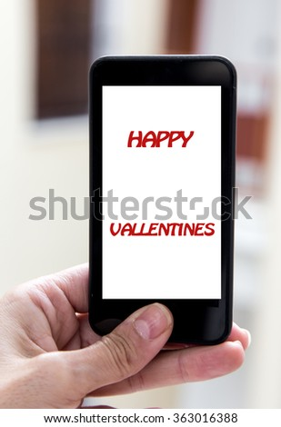 Woman hands holding mobile phone with sign valentines day