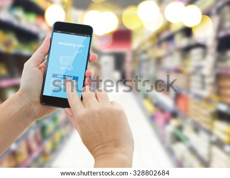 woman hands holding mobile smart phone with mobile shop  on supermarket blur background  - e-commerce concept - stock photo