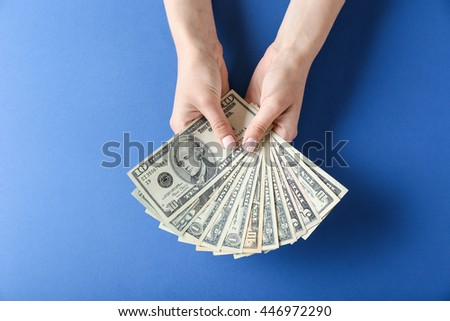 Woman hands holding money on blue background - stock photo