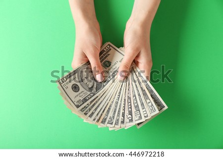 Woman hands holding money on green background - stock photo
