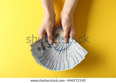 Woman hands holding money on yellow background - stock photo